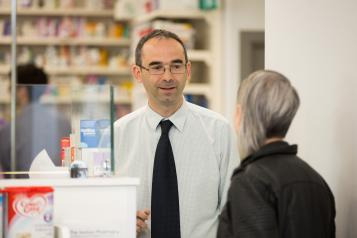 Woman speaking to a male pharmacist